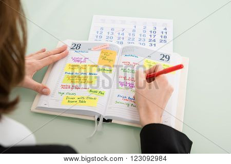 Businesswoman With Calendar Writing Schedule In Diary
