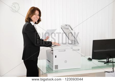Businesswoman Copying Paper On Photocopy Machine