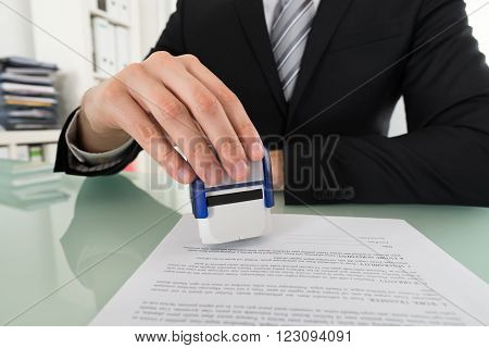Close-up Of Businessman Hand Using Stamper On Document