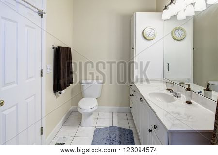 Simple white bathroom with tile and marble sink