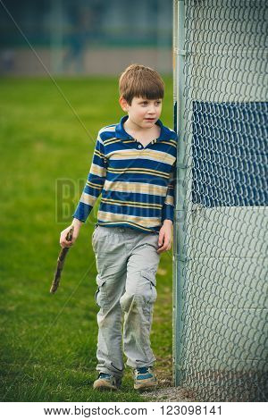 Autistic boy with stick wearing striped shirt. Outside next to fence.