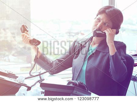 Businesswoman Sitting at her Desk Answering a Telephone Call from a Customer Vintage Tone