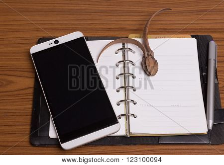 Diary note with smartphone on wood background (Organizer agenda book diary)