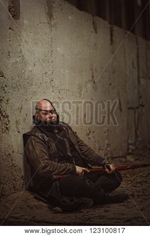 Portrait Of Adult Bald Man Sitting With A Gun Near Concrete Wall