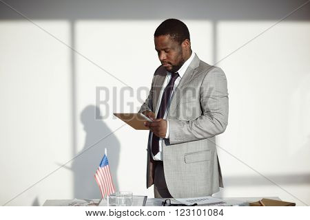 African businessman working with his touchpad at office