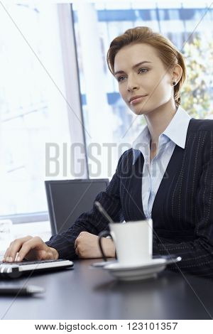 Attractive businesswoman sitting at desk, daydreaming. Cup of coffee in foreground.