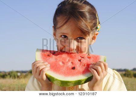 Smiling little girl eating watermelon on field