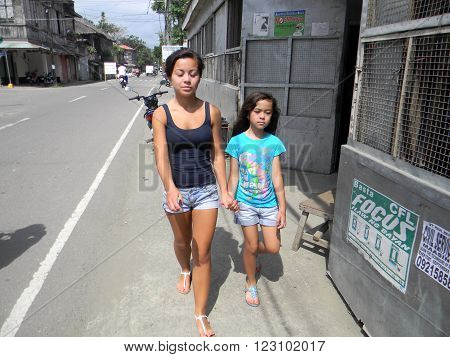 MAASIN, SOUTHERN LEYTE, PHILIPPINES / AUGUST 2, 2011: Two girls walk through the streets of Maasin in Southern Leyte.