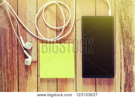 Closeup of black smartphone with headphones and sticky notes on wooden surface, Square image format Instant photo split toning color effect, Vintage style