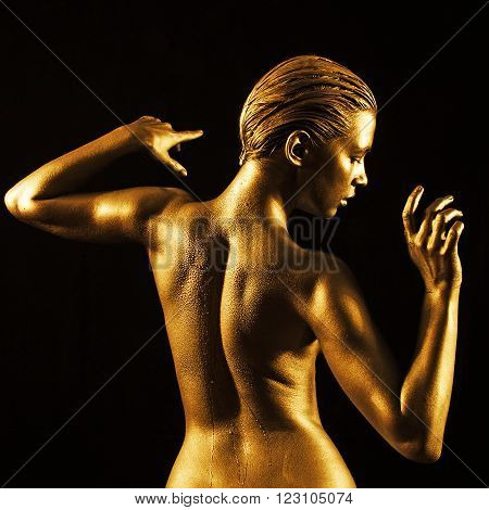 Lovely young woman in gold with naked back