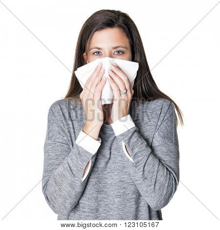 Beautiful young woman blowing her nose with a tissue