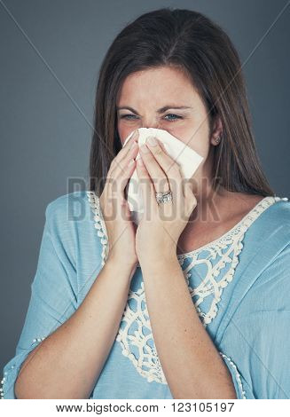 Woman blowing her nose hard