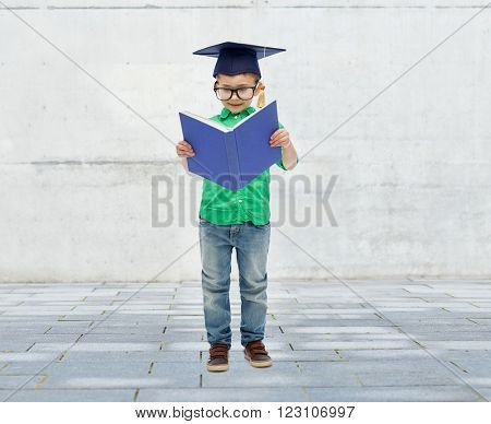 childhood, school, education, knowledge and people concept - happy boy in bachelor hat or mortarboard and eyeglasses over urban city street background