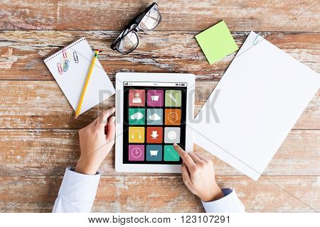 business, education, people and technology concept - close up of female hands pointing finger to menu icons on tablet pc computer screen, papers and eyeglasses