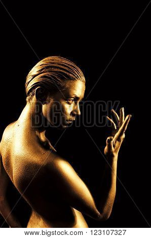 Beautiful young naked woman in gold looks at his hand