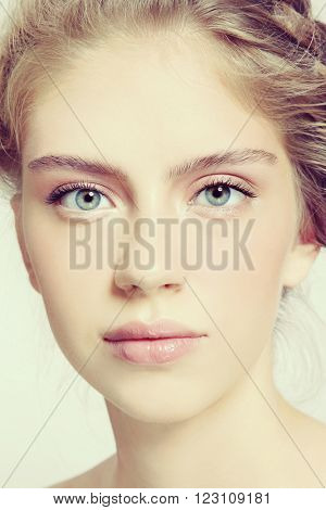 Vintage style close-up portrait of young beautiful healthy girl with clean make-up and braids