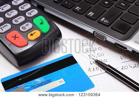 Payment terminal with contactless credit card laptop and financial calculations credit card reader finance concept