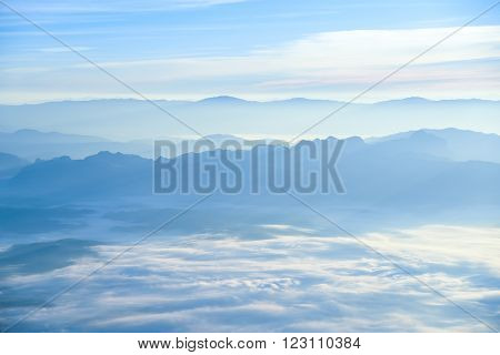 Beautiful layers of mountain range landscape with winter sky from top view in majestic sunrise and fog