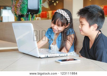 Asian girl and boy use laptop and smartphone in canteen.