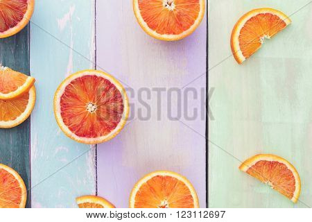 Halved and wedge oranges and blood oranges on rustic board. Top view, vintage toned image, blank space