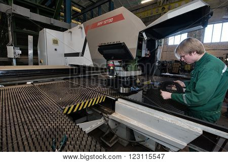 Saint-Petersburg Russia - March 23 2016: Worker young man miller is working by milling machine in working overalls shop engineering plant. The large milling machine.