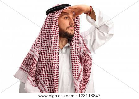 Young Arab with a checkered veil looking in the distance and shading his eyes with his hand isolated on white background