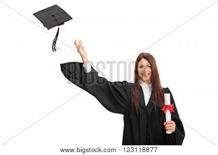 Joyful female graduate student holding a diploma and throwing her graduation hat isolated on white background