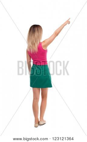 Back view of pointing woman. beautiful girl. Rear view people collection. backside view of person.  Isolated over white background. blonde in a green skirt and red sweater saw something interesting.