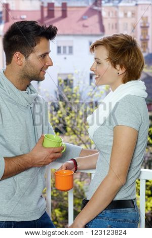 Young loving couple having coffee at the balcony, smiling. Side view.