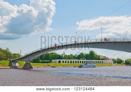 VELIKY NOVGOROD, RUSSIA - JULY 17, 2012: Pedestrian bridge over The Volkhov River. On the background is Trade Arcade. The bridge connects the Kremlin side and Yaroslav's Court