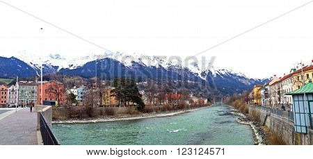 Inn river in Innsbruck city with colorful buildings in front of the high mountains