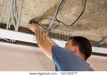 Man Repairing Electrical Wiring On Ceiling