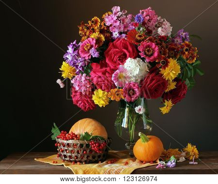 Still life with garden flowers in a glass vase pumpkins and viburnum on a dark background from boards.