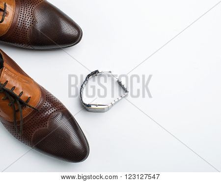 Men's shoes and watches over white background