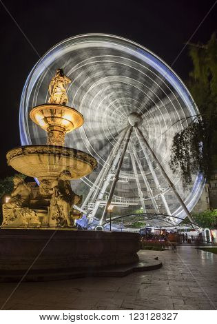 BUDAPEST, HUNGARY, JULY 9, 2015: Danubius fountain and Sziget's Eye (ferris wheel) at Erzsebet Square. Erzsebet square is the largest green area in Budapest's inner city.