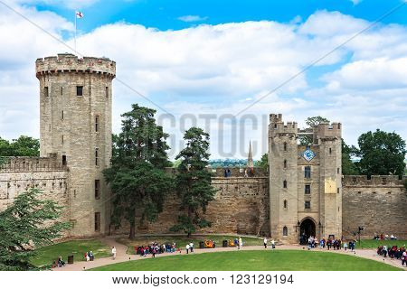 Warwick United Kingdom - June 21 2006: View of the Medieval castle tower and gatehouse from within the castle gardens and people enjoying the setting Warwick Warwickshire