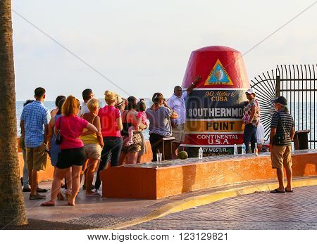 KEY WEST, USA - MAY 10, 2015: People standing in line to take a picture of themselves at the replica of a buoy claiming to be the Southernmost Point Continental USA.
