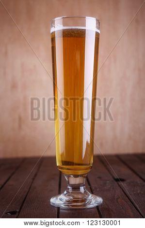 Pilsner vase glass with light beer on a grunge wood background