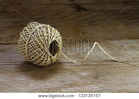 Ball of string on a rustic wooden background with copy space close up showing texture and strands