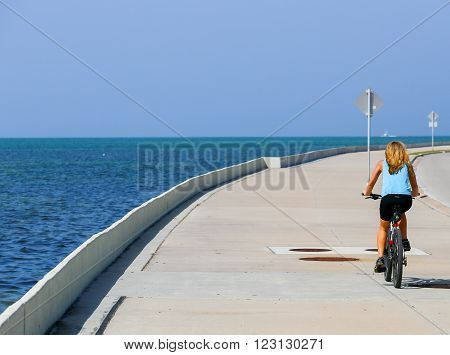 KEY WEST, USA - MAY 10, 2015: A woman cycling in the sun on the Florida Keys Overseas Heritage Trail. To her left side the blue sea above the blue sky.