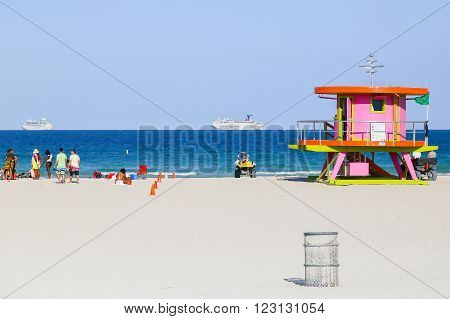 MIAMI BEACH, USA - MAY 9, 2015: A beach section with a pink lifeguard station and some people sitting or standing, a trash can in front and two cruise liners on the ocean in the back.
