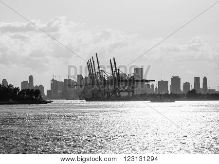 MIAMI BEACH, USA - MAY 9, 2015: The entrance to the Port of Miami with a tugboat and the skyline in the back. Captured in black and white.