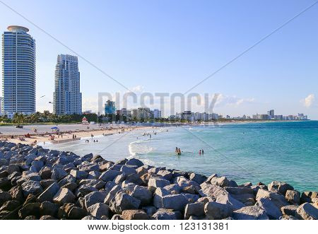MIAMI BEACH, USA - MAY 9, 2015: People sunbathing and swimming at the beach in the evening a jetty in front and the skyline in the back.