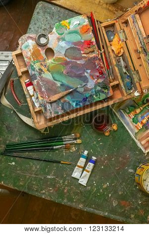 Workplace of the artist with brushes, oil paints, pallete and palette knife