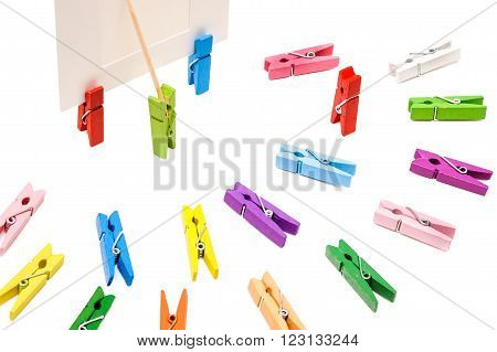Clothespin is shows a toothpick on a white frame. Other colored pegs arranged in a semicircle.One is standing