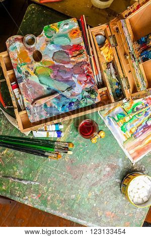 Bright workplace of the artist with brushes, oil paints, pallete, palette knife and tea with lump sugar
