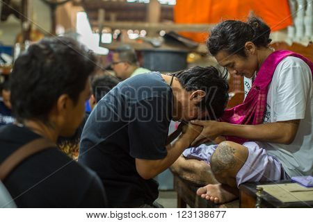WAT BANG PHRA, THAILAND - MAR 18, 2016: Unidentified monk master Yantra tattoo during Wai Kroo Master Day Ceremony in Bang Pra monastery, about 50 km west of Bangkok.
