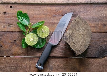Green lemons with knife on hard wood