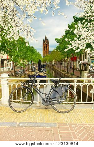 Bike on bridge and Canal with Old Church tower of Delft, Holland