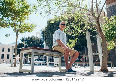 Relaxed Senior Man Sitting On A Bench